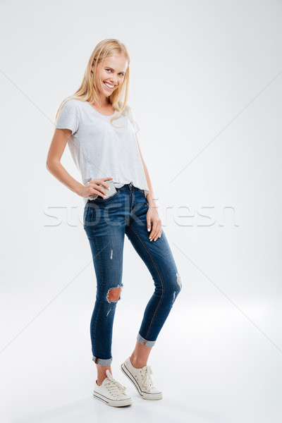 Beautiful young blonde girl putting smartphone in the jeans pocket Stock photo © deandrobot