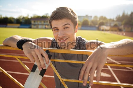 Young sportsman with bottle of water resting on the railing Stock photo © deandrobot