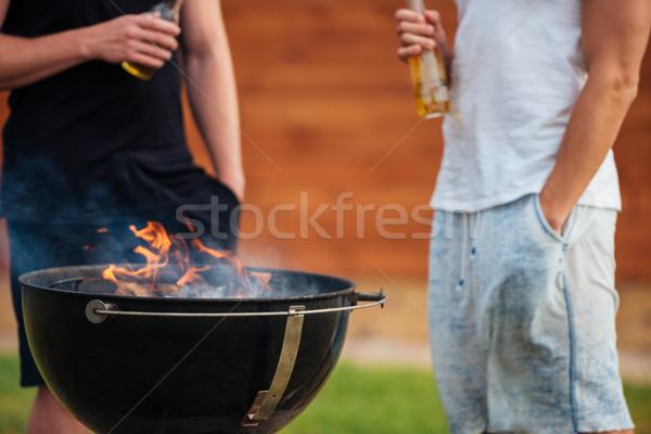Kép két férfi tart sör üvegek barbecue Stock fotó © deandrobot