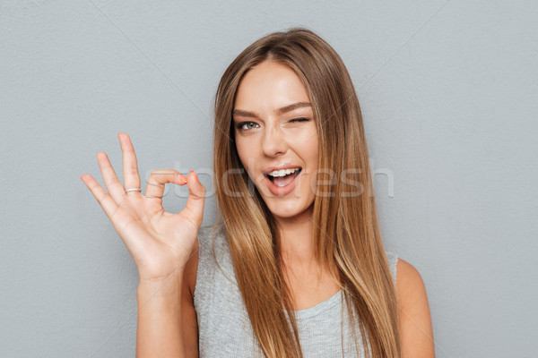 Happy young woman showing ok sign with fingers isolated Stock photo © deandrobot