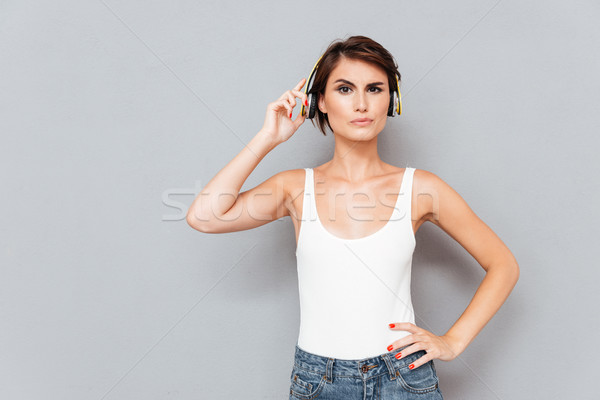 Unhappy woman listening music too loud and removing yellow headphones Stock photo © deandrobot