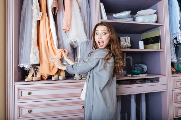Young woman searching what to wear in a closet Stock photo © deandrobot