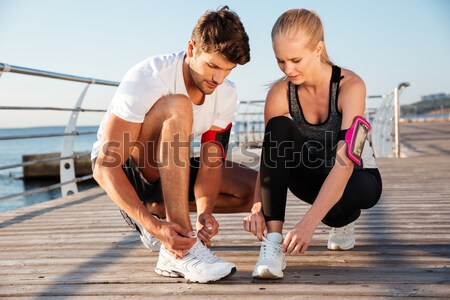 Young sports woman and man doing plank exercise together outdoors Stock photo © deandrobot
