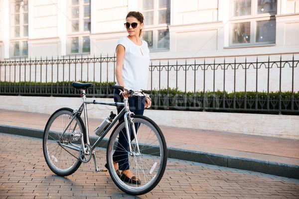 Toevallig brunette vrouw fietser permanente fiets Stockfoto © deandrobot
