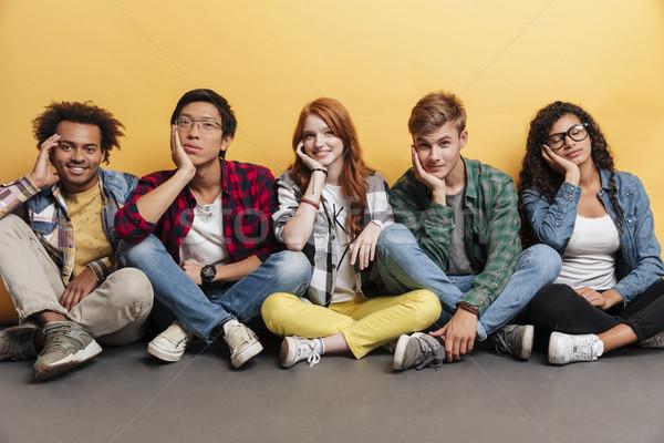 Groupe souriant jeunes séance jambes croisées Photo stock © deandrobot