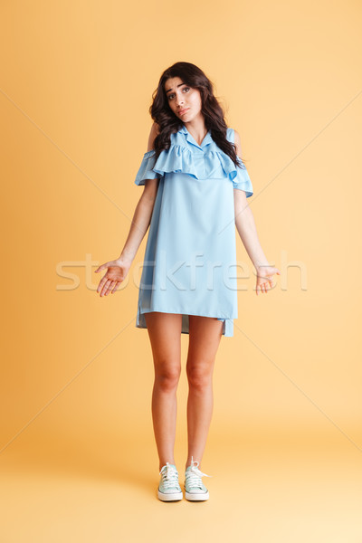 Full length portrait of a young woman shrugging shoulders Stock photo © deandrobot