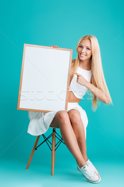 Stock photo: Woman pointing finger at blank board while sitting on chair
