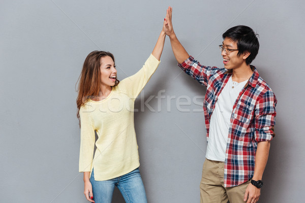Portrait of a beautiful couple standing and giving high five Stock photo © deandrobot