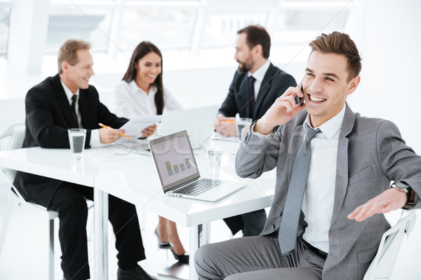 Portrait of young business man by the table with colleagues Stock photo © deandrobot