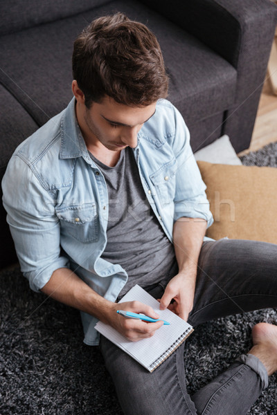 Portrait of a young casual man making notes in copybook Stock photo © deandrobot