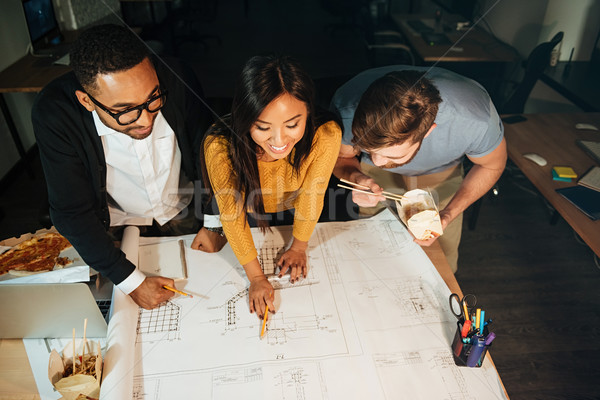 Photo of happy architects working late at night Stock photo © deandrobot