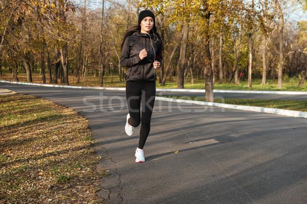 Fiatal hölgy meleg ruházat fülhallgató fut Stock fotó © deandrobot