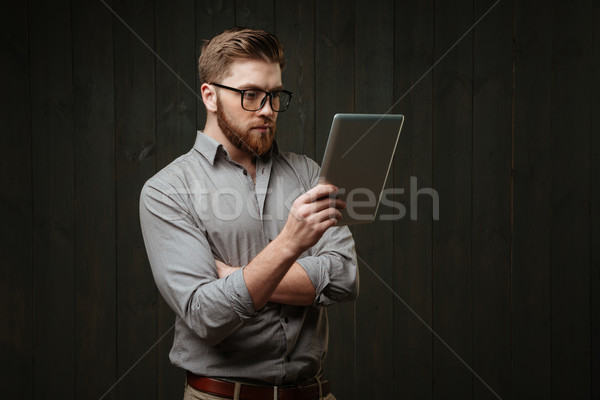 Man in eyeglasses looking at tablet computer in his hand Stock photo © deandrobot