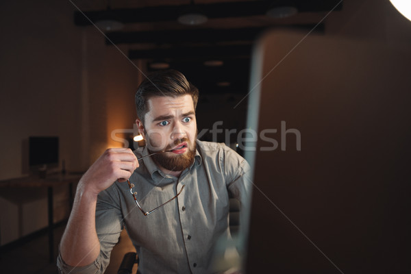 Confused designer working and looking at computer. Stock photo © deandrobot