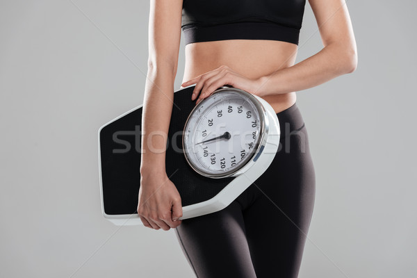 Closeup of sportswoman standing and holding weighing scale Stock photo © deandrobot