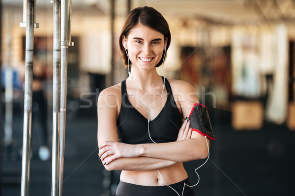 Happy sportswoman with armband listening to music in gym Stock photo © deandrobot