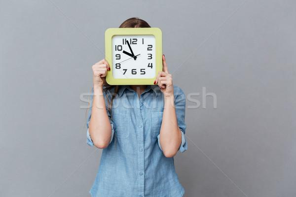 Fiatal nő póló rejtőzködik mögött óra stúdió Stock fotó © deandrobot