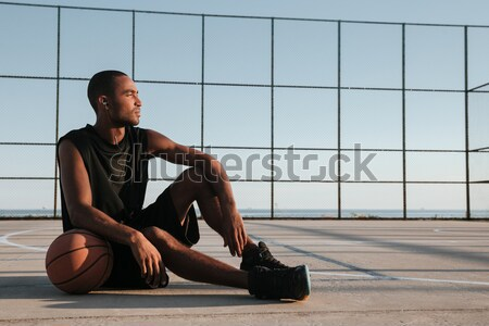 African sportsman resting at the playground with basketball Stock photo © deandrobot