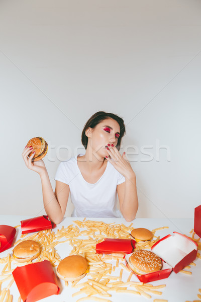 Fáradt fiatal nő eszik hamburger ásít asztal Stock fotó © deandrobot