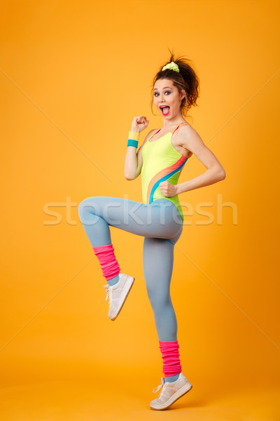 Full length of cheerful young sportswoman running and doing exercises Stock photo © deandrobot