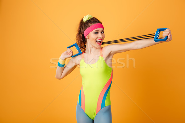 Smiling beautiful young sportswoman doing exercises with expander Stock photo © deandrobot