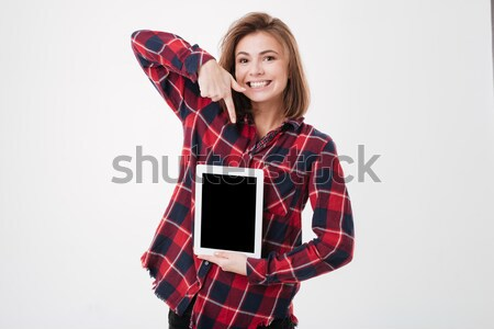 Cheerful cute woman pointing finger on blank screen tablet Stock photo © deandrobot