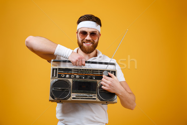 Cheerful young man wearing sunglasses holding tape recorder Stock photo © deandrobot