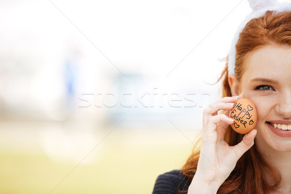 Cropped image half face of a young red head girl Stock photo © deandrobot