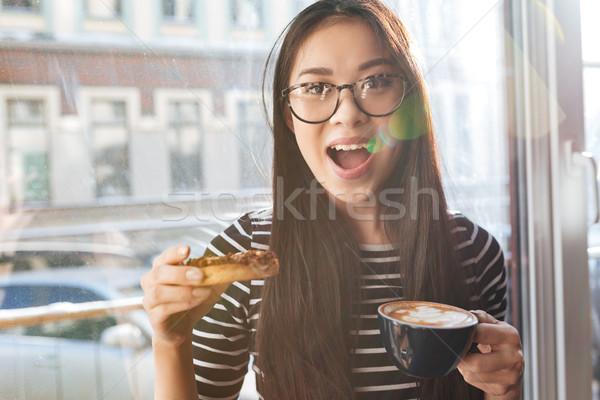 Pretty Asian woman eating cake on windowsill Stock photo © deandrobot