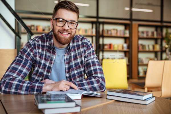 Smiling young student sitting at the desk in library Stock photo © deandrobot