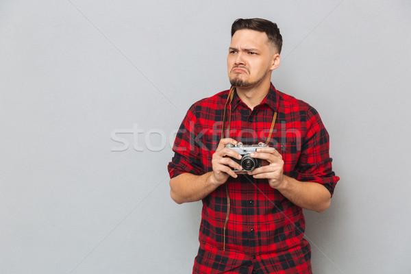 Displeased man in shirt holding retro camera Stock photo © deandrobot
