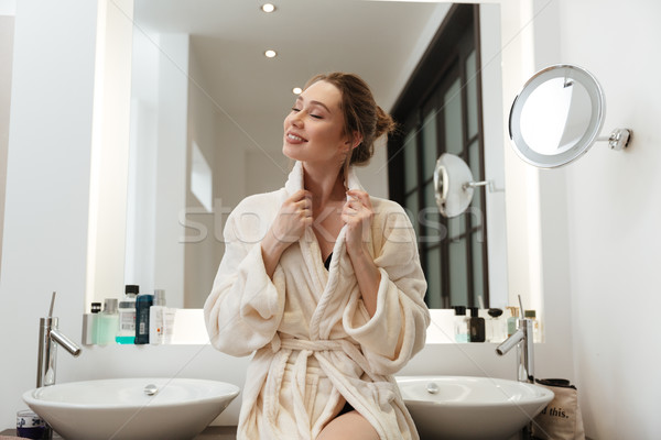 Smiling relaxed young woman in bathrobe standing in bathroom Stock photo © deandrobot