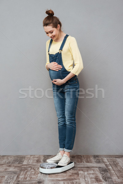 Pretty pregnant lady standing on scales Stock photo © deandrobot