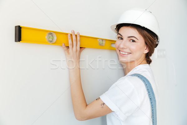 Close up portrait of a smiling woman builder in hardhat Stock photo © deandrobot