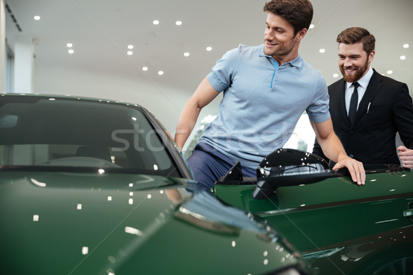 Young male customer getting inside his new car Stock photo © deandrobot