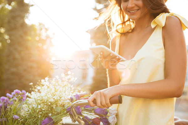 Cropped image of a girl in dress using mobile phone Stock photo © deandrobot
