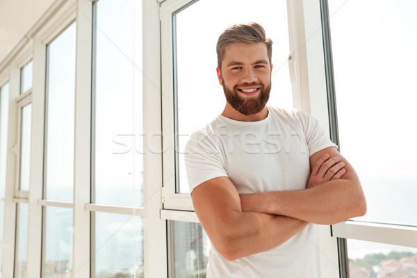 Happy bearded man with crossed arms standing near the window Stock photo © deandrobot