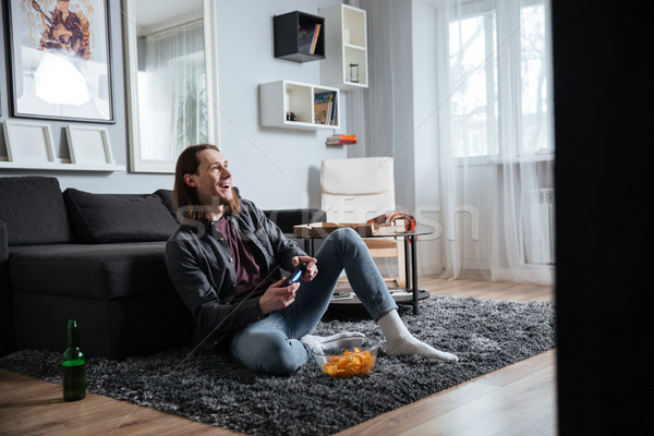 Happy man sitting at home indoors play games with joystick Stock photo © deandrobot