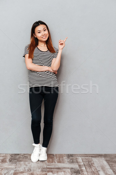 Cheerful young pretty woman pointing. Stock photo © deandrobot