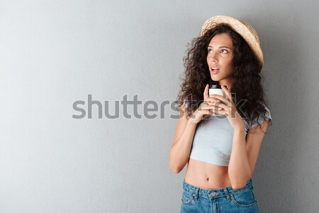 Pleased curly woman in hat drinking coffee with closed eyes Stock photo © deandrobot