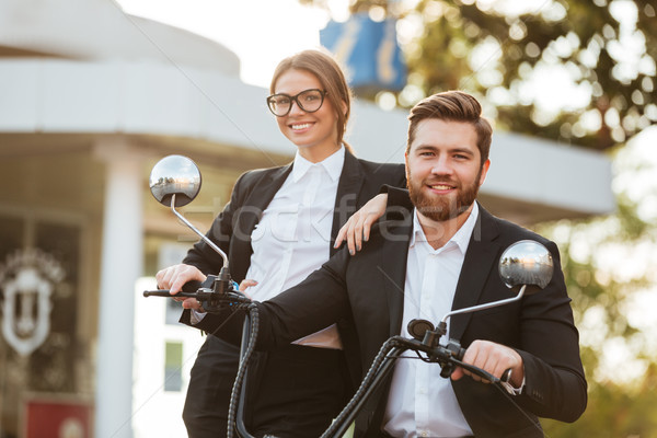 Happy business couple posing with modern motorbike outdoors Stock photo © deandrobot