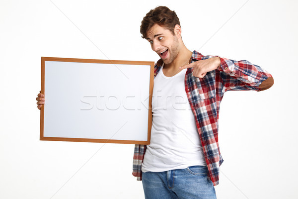Portrait of an excited guy pointing finger at blank board Stock photo © deandrobot