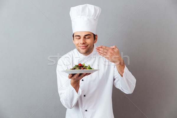 Handsome young cook in uniform smell salad Stock photo © deandrobot