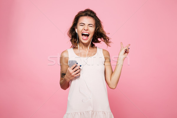 Portrait of a happy positive girl listening music with earphones Stock photo © deandrobot