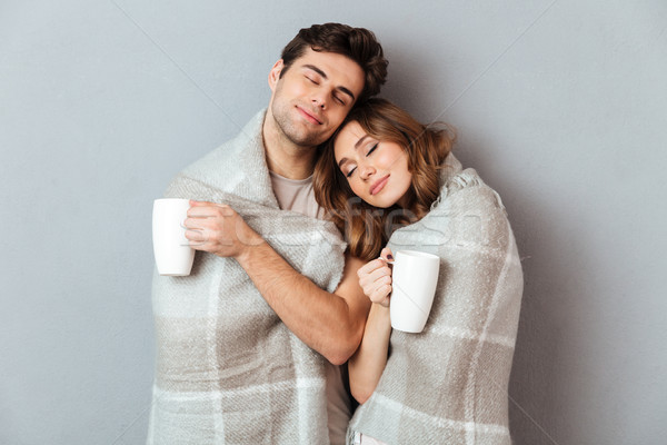 Stock photo: Portrait of a lovely happy couple standing wrapped in blanket