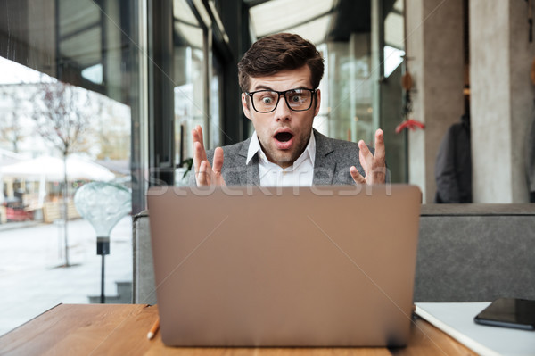 Shocked business man in eyeglasses sitting by table in cafe Stock photo © deandrobot