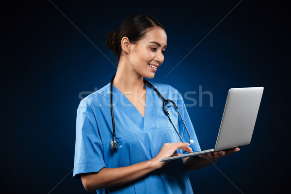 Cheerful lady in medical uniform using laptop and looking camera Stock photo © deandrobot