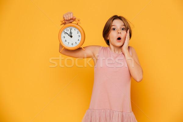 Megrémült lány mutat ébresztőóra néz kamera Stock fotó © deandrobot