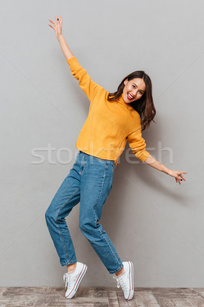 Full length image of Happy brunette woman in sweater Stock photo © deandrobot