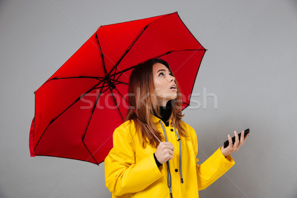 Portrait of a pretty girl dressed in raincoat Stock photo © deandrobot